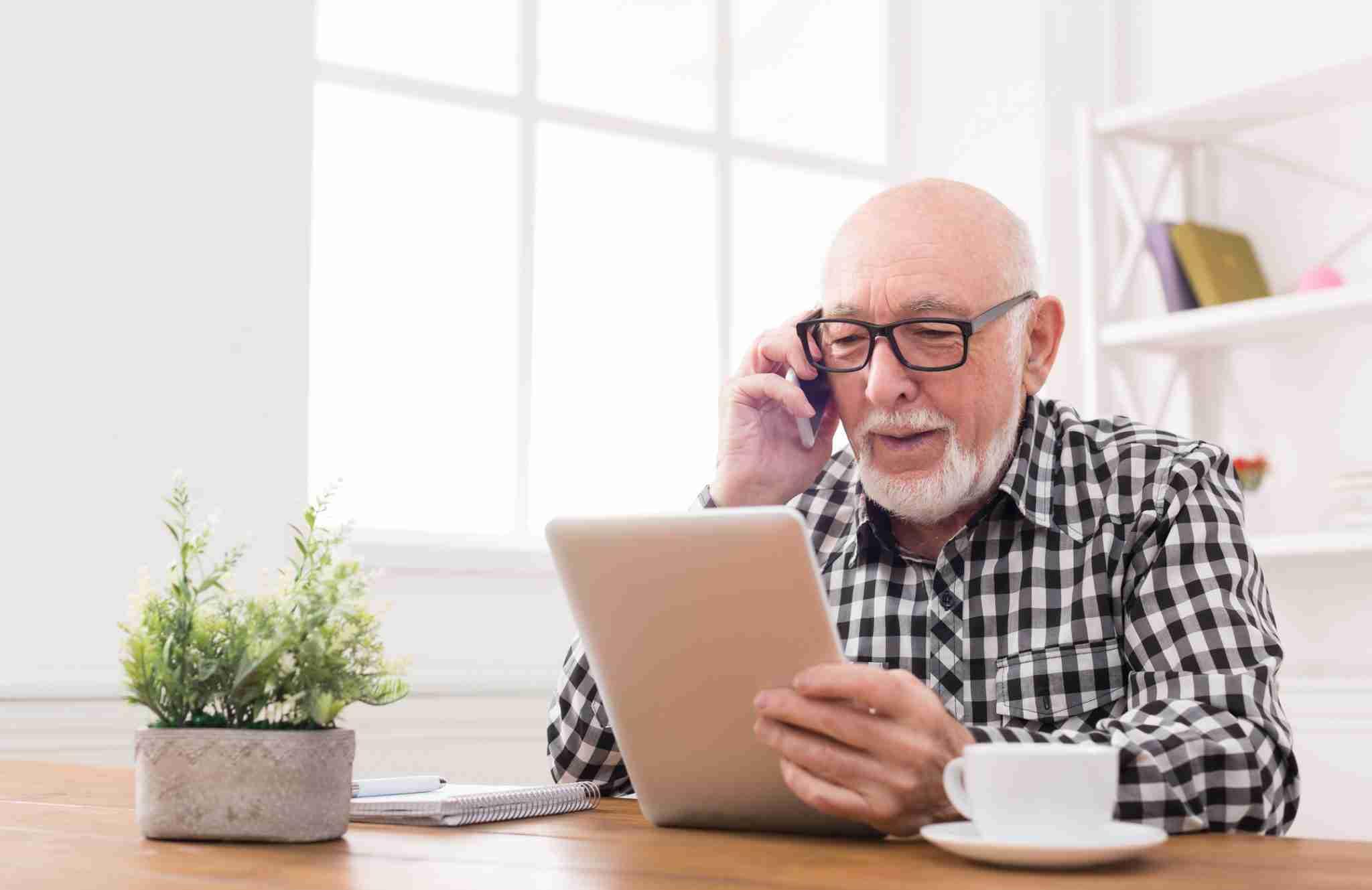 Man with white beard talking on phone